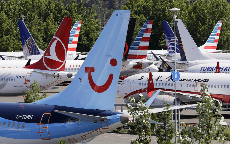 Dozens of grounded Boeing 737 MAX airplanes, including one for TUI Airlines, center, crowd a parking area adjacent to Boeing Field Thursday, Aug. 15, 2019, in Seattle. Aviation authorities around the world grounded the plane in March after two fatal crashes. (AP Photo/Elaine Thompson)