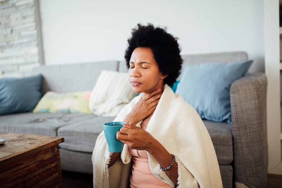 woman, fallen ill is staying at home wrapped in a blanket socially distancing and quarantining herself, feeling her throat hurt and being sore, having a cup of hot tea