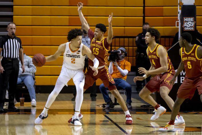 Oklahoma State guard Cade Cunningham (2) drives the lane against Iowa State guard Rasir Bolton (45), George Conditt IV (4) and Jalen Coleman-Lands (5) during the first half of the NCAA college basketball game in Stillwater, Okla., Tuesday, Feb. 16, 2021. (AP Photo/Mitch Alcala)