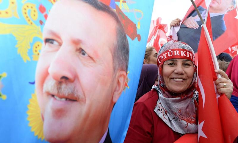 Supporters of Turkish President Tayyip Erdogan wave national flags as they wait for his arrival at the Presidential Palace