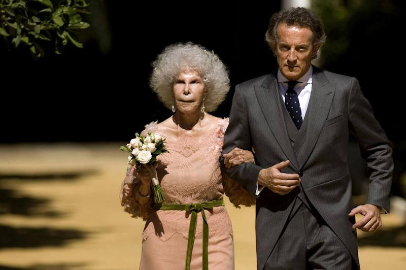 Spain's Duchess of Alba, Maria del Rosario Cayetana Fitz-James-Stuart and her husband Alfonso Diez walk towards photographers after their wedding ceremony at the Palacio de las Duenas in Sevilla on October 5, 2011. Spain's fabulously wealthy 85-year-old Duchess of Alba marries a civil servant 25 years her junior in a story of love and riches that has gripped the nation. The twice-widowed aristocrat, renowned for her frizzy hair, glamorous social life and colourful dress sense, is tying the knot in the chapel of her 15th century Palacio de las Duenas in Sevilla. AFP PHOTO / Jorge Guerrero (Photo credit should read Jorge Guerrero/AFP via Getty Images)