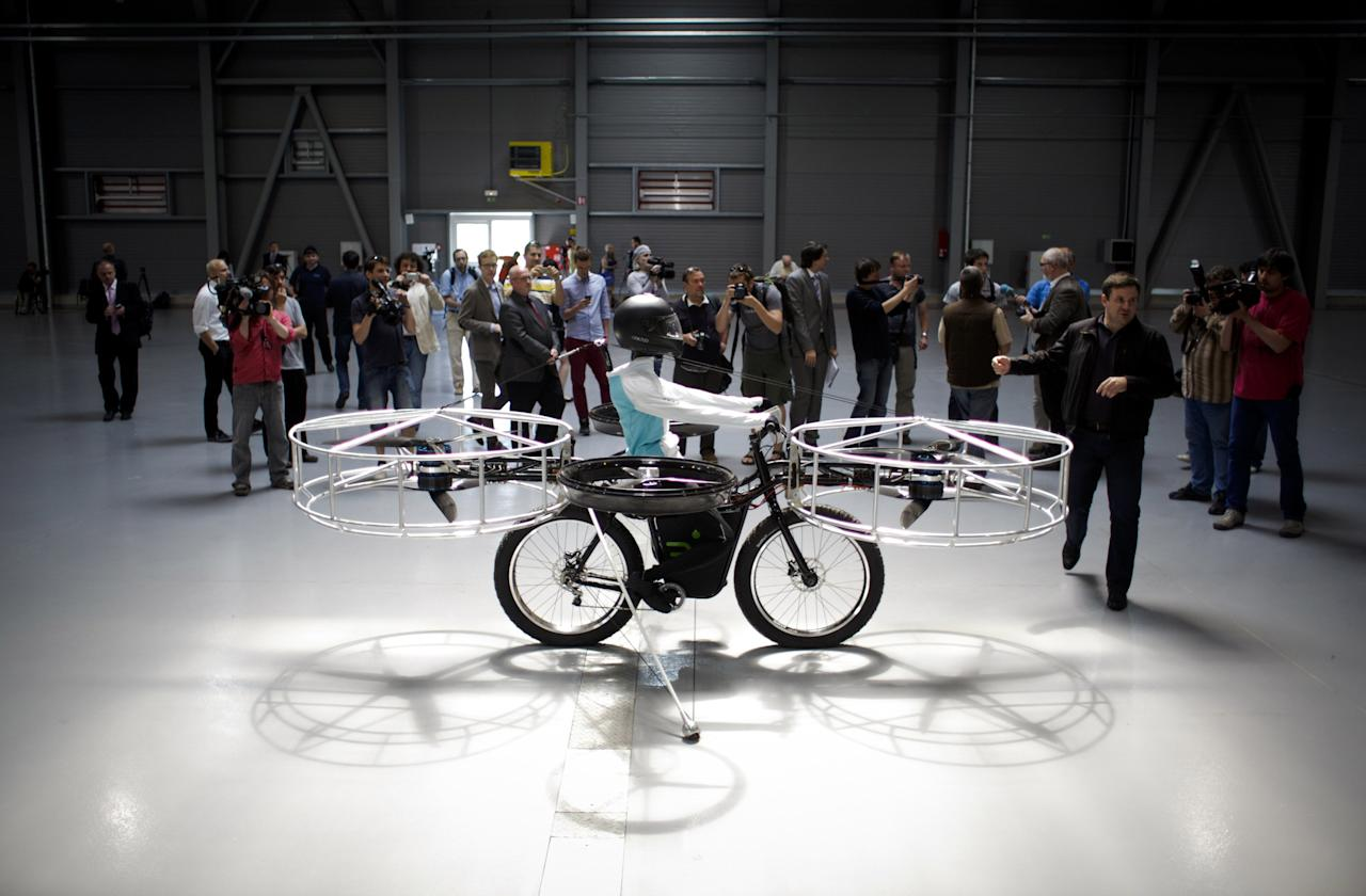 Journalists look at a 'Flying bike' bicycle ahead of its first public flight on June 12, 2013 in Prague, Czech Republic. The bike has been manufactured by 3 different companies from the Czech Republic (Duratec, Technodat, Evektor) and has been supported by French Company Dassault System. The F-Bike has four main motors (10kW) and two stabilization motors (3,5 kW). It has an estimated constant flight time of 3-5 minutes.  (Photo by Matej Divizna/Getty Images)