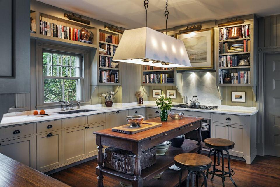"<p>Traditionalists will swoon for an oversize shaded light fixture to reside over the kitchen island for a cozier space. This kitchen, designed by <a href=""https://dcwarchitects.com/"" rel=""nofollow noopener"" target=""_blank"" data-ylk=""slk:Douglas C. Wright Architects"" class=""link rapid-noclick-resp"">Douglas C. Wright Architects</a>, offers ample space for the owner's cookbook collection and creates a delightful space to brush up on one's culinary skills or get inspired for next week's menu. </p>"