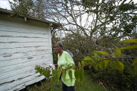 Wyna Dennis shows the damage to her home from fallen trees before she leaves Lake Charles, La., in the aftermath of Hurricane Laura, Sunday, Aug. 30, 2020. (AP Photo/Gerald Herbert)