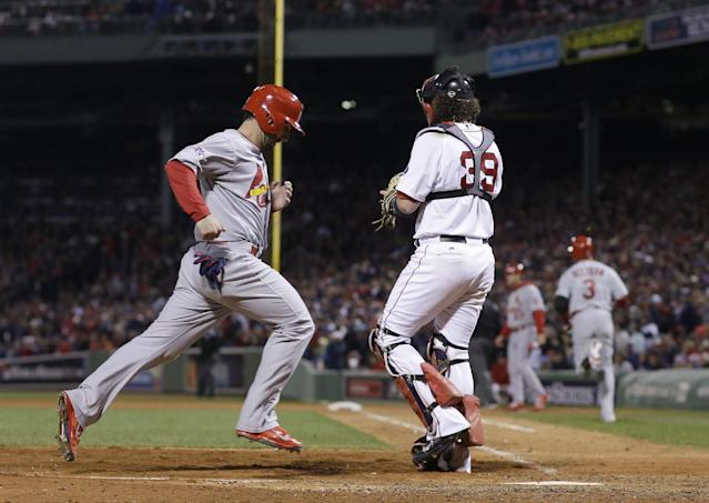 St. Louis Cardinals' Daniel Descalso scores past Boston Red Sox catcher Jarrod Saltalamacchia (39) on a hit by Carlos Beltran during the seventh inning of Game 2 of baseball's World Series Thursday, Oct. 24, 2013, in Boston. (AP Photo/Matt Slocum)