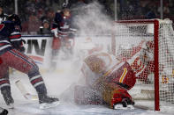 Winnipeg Jets' Gabriel Bourque (57) sprays snow on Calgary Flames' goaltender David Rittich (33) during the second period of an NHL Heritage Classic outdoor hockey game in Regina, Canada, Saturday, Oct. 26, 2019. (Liam Richards/The Canadian Press via AP)