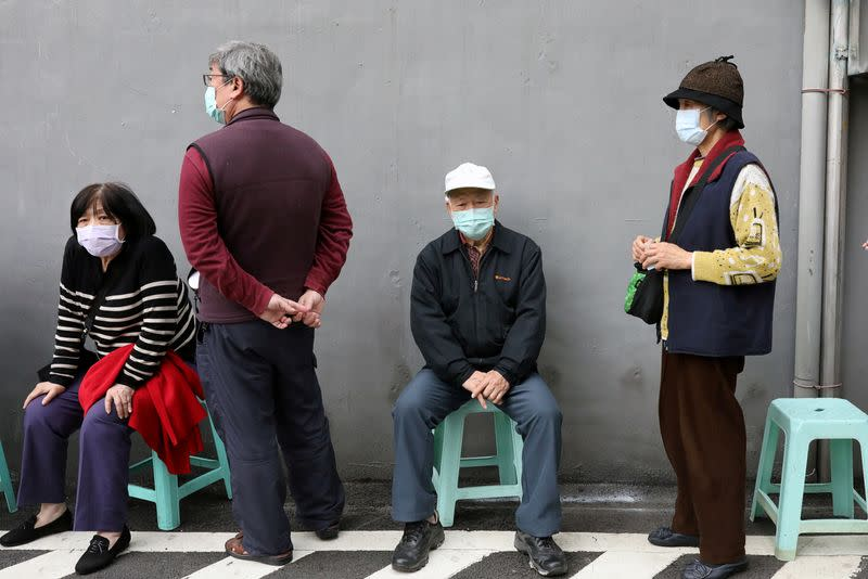People wait in long lines to buy face masks in order to protect themselves from the coronavirus disease (COVID-19), outside a pharmacy in Taipei