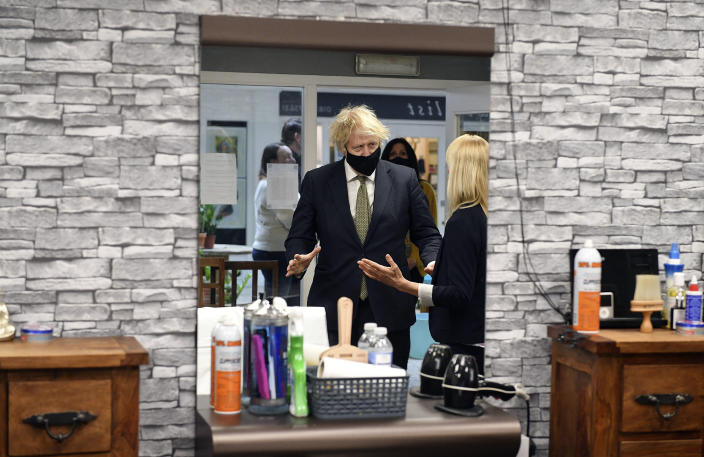 Britain's Prime Minister Boris Johnson in Lemonheads Barber shop during a visit to Lemon Street Market in Truro, England, Wednesday, April 7, 2021 to see how they are preparing to reopen ahead of Step 2 of the roadmap on Monday. Johnson has confirmed that businesses from barbers to bookstores will be allowed to reopen next week and that Britain's slow but steady march out of a three-month lockdown remains on track. (Justin Tallis/Pool Photo via AP)