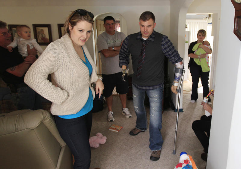 Army Staff Sgt. Travis Mills prepares to step outside his boyhood home in Vassar, Mich., Thursday, Oct. 4, 2012 as family and friends look on. Mills is visiting his hometown for the first time since losing all four limbs while fighting in Afghanistan. Mills, his wife, Kelsey, and their 1-year-old daughter, Chloe, will be the grand marshals of Vassar High School's homecoming parade on Thursday evening. (AP Photo/Carlos Osorio)