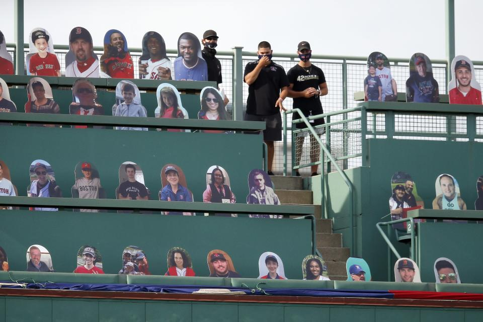 Boston Red Sox employees stand in the Green Monster seats with cutouts of former players and fans before an opening day baseball game between the Red Sox and the Baltimore Orioles at Fenway Park, Friday, July 24, 2020, in Boston. (AP Photo/Michael Dwyer)