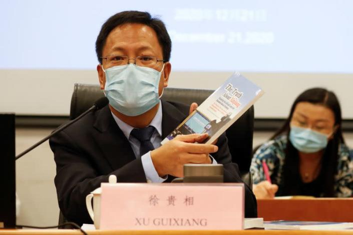 Xu Guixiang, deputy head of Xinjiang's publicity department holds a copy of a booklet, as he speaks during a news conference in Beijing