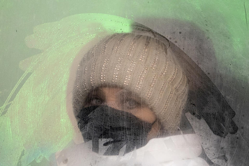 A woman wearing a face mask to help protect herself from the coronavirus looks from a fogged bus window in Ivano-Frankivsk, Western Ukraine, Friday, Jan. 8, 2021. The country of 42 million is recording about 9,000 new COVID-19 infections a day; more than 19,500 people have died. Ukraine imposes a wide-ranging lockdown beginning Friday, closing schools and entertainment venues and restaurant table service through Jan. 25. (AP Photo/Evgeniy Maloletka)