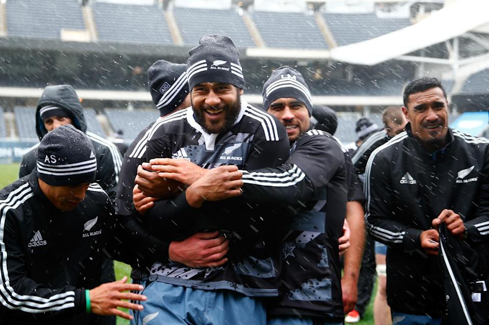 Patrick Tuipulotu of New Zealand's All Blacks (C) is hugged by Aaron Smith (L) and Liam Messam, to keep warm in the freezing conditions during the Captain's Run, at Soldier Field in Chicago, Illinois, on October 31, 2014 (AFP Photo/Phil Walter)