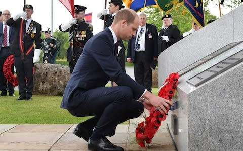 Prince William lays a wreath in the pouring rain - Credit: Anthony Devlin/AFP