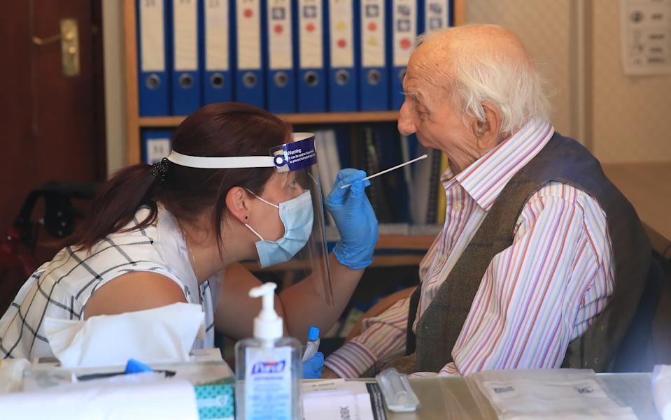 Assistant manager Claire Welford administers a coronavirus swab test on resident Harry Hall, 94, at the Eothen Homes care home in Whitley Bay, Tyneside, where all staff and residents are being tested for coronavirus.