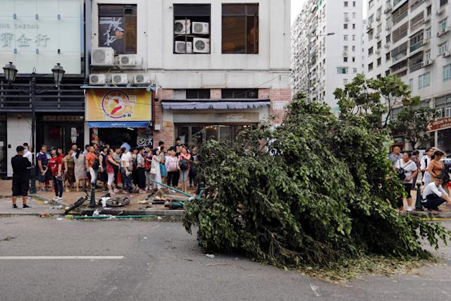 <p>Tourists from China lineup outside a jewelry shop where a tree was uprooted by strong winds from Typhoon Hato in Macau, China, Aug. 24, 2017. (Photo: Tyrone Siu/Reuters) </p>