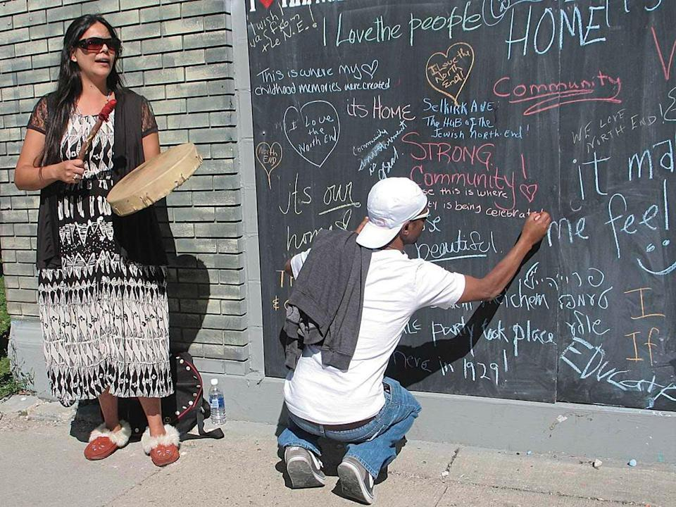 A woman drums while a young man writes on a chalk wall.