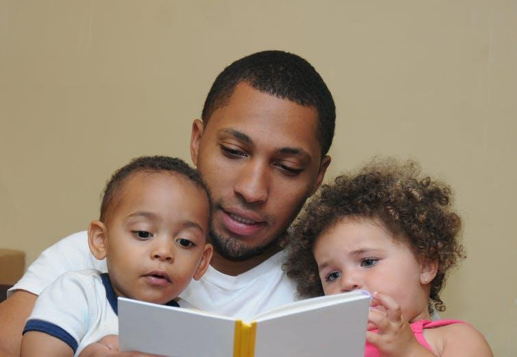 Man reads to two children.