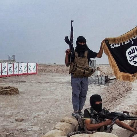 <span>Isil militants pose with the jihadists' flag after they seized an Iraqi army checkpoint in the northern Iraqi province of Salahuddin in 2014</span> <span>Credit: AFP </span>