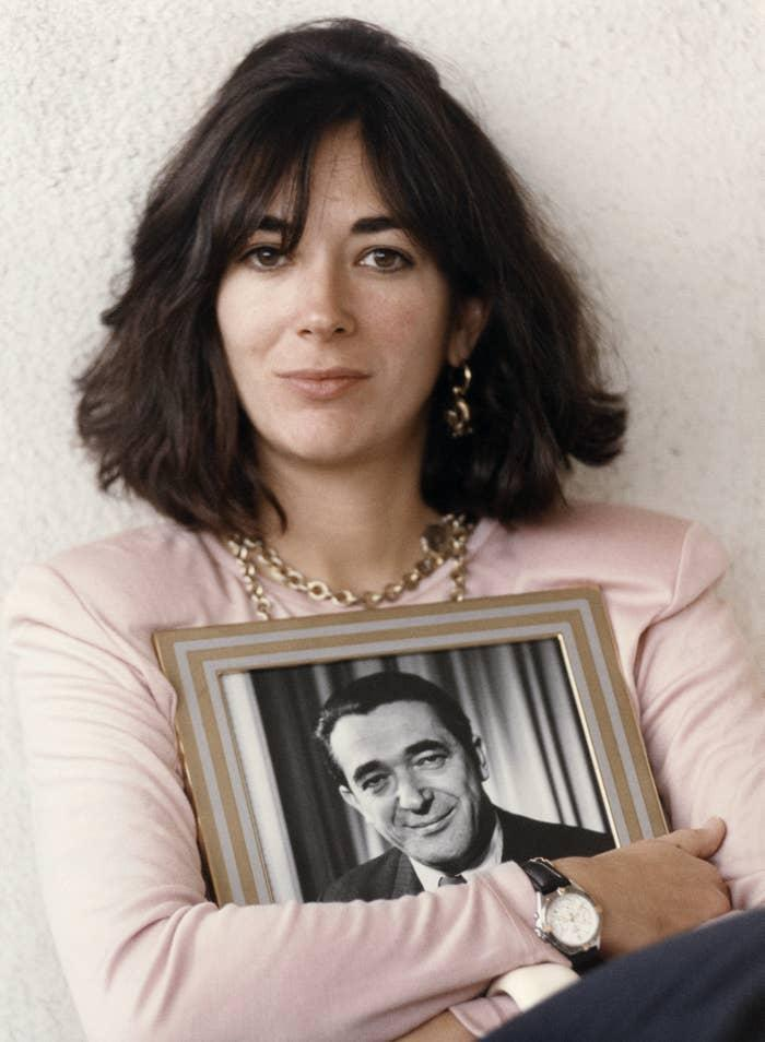 Ghislaine Maxwell in 1991, holding a framed photograph of her late father