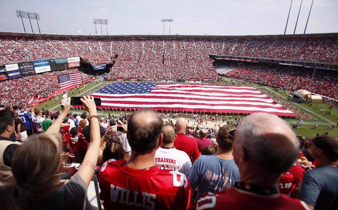Fans listen to the national anthem as a U.S. flag is displayed during a ceremony before an NFL football game between the San Francisco 49ers and the Seattle Seahawks in San Francisco, Sunday, Sept. 11, 2011. (AP Photo/Aaron Kehoe)