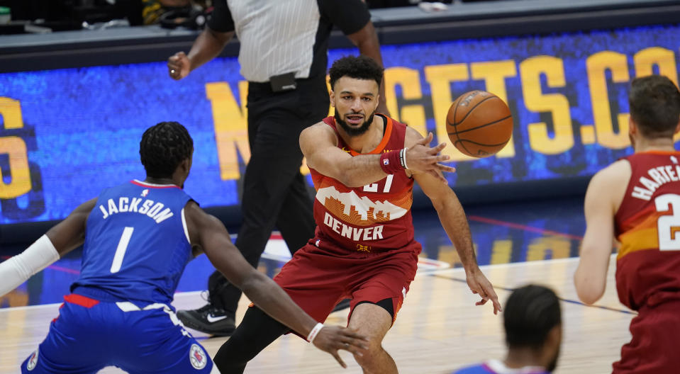 Denver Nuggets guard Jamal Murray, center, passes the ball to center Isaiah Hartenstein, right, as Los Angeles Clippers guard Reggie Jackson defends during the first half of an NBA basketball game Friday, Dec. 25, 2020, in Denver. (AP Photo/David Zalubowski)