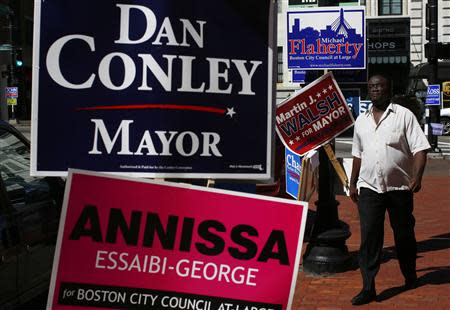 A pedestrian walks by campaign signs outside a polling station in Boston, Massachusetts