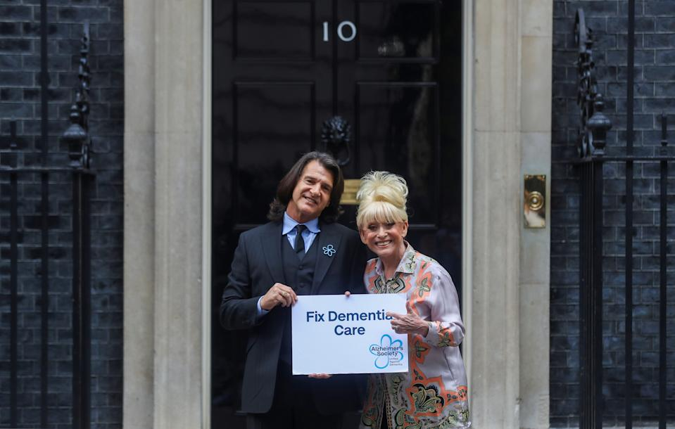 LONDON, ENGLAND - SEPTEMBER 02: Television actor Barbara Windsor and her husband Scott Mitchell pose with a placard in front of Downing Street ahead of a meeting with Britain's Prime Minister Boris Johnson in London on September 2, 2019 in London, England. Barbara Windsor, who suffers from Alzheimers, met with the Prime Minister at 10 Downing Street to discuss dementia care. (Photo by Simon Dawson - WPA Pool/Getty Images)