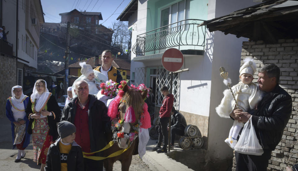 Families prepare to take part in a mass circumcision ceremony in the village of Ribnovo, Bulgaria, Sunday, April 11, 2021. Despite the dangers associated with COVID-19 and government calls to avoid large gatherings, Hundreds of people flocked to the tiny village of Ribnovo in southwestern Bulgaria for a four-day festival of feasting, music and the ritual of circumcision which is considered by Muslims a religious duty and essential part of a man's identity. (AP Photo/Jordan Simeonov)