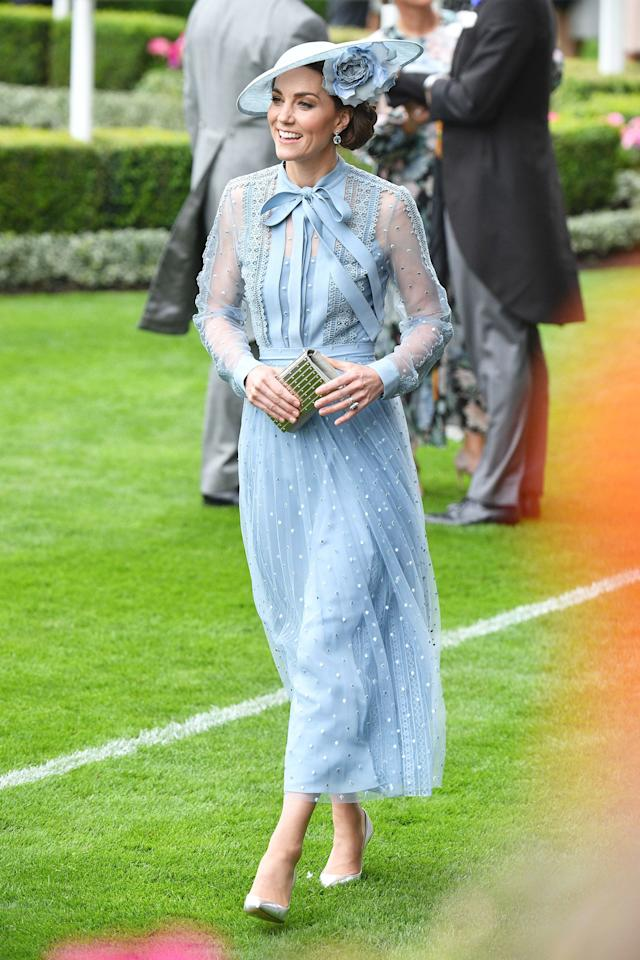 "The insider adds, ""She looks amazing, and she is getting lots of compliments about it.""  The royal was radiant in a cornflower blue dress with sheer sleeves by Ellie Saab and a matching Philip Treacy hat with a flower detail for Royal Ascot in June."