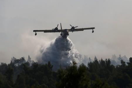 A firefighting plane makes a water drop as a wildfire burns near the village of Stavros on the island of Evia
