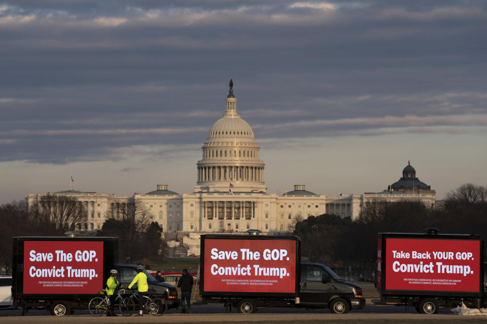 Billboard trucks parked on the National Mall near of the U.S. Capitol during the impeachment trial of former President Donald Trump in Washington, Tuesday, Feb. 9, 2021. (AP Photo/Jose Luis Magana)