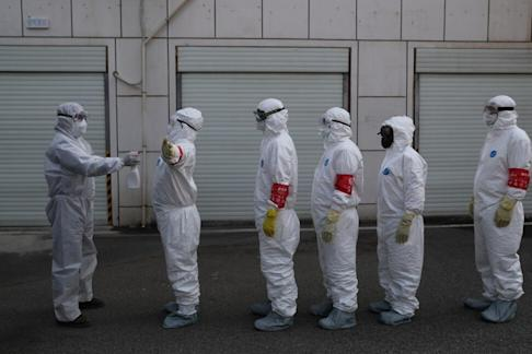 Volunteers in protective suits line up to be sprayed with disinfectant in Wuhan, the epicentre of the novel coronavirus outbreak, in February. Photo: Reuters