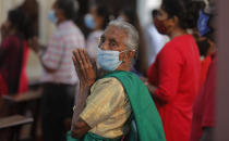 An elderly Sri Lankan Christian wearing a mask as a precaution against the coronavirus prays inside a church on Christmas in Colombo, Sri Lanka, Friday, Dec. 25, 2020. (AP Photo/Eranga Jayawardena)