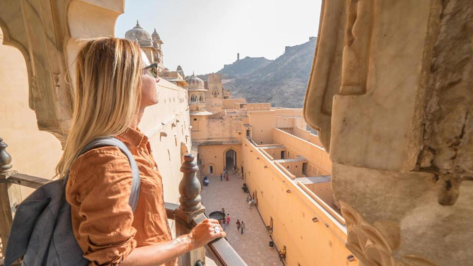 Young woman traveling in India contemplating ancient temple in Jaipur, India.