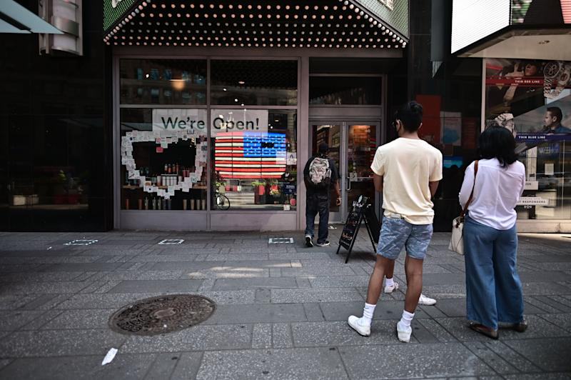 The American flag is reflected in a Cafe as people queue for coffee at Times Square as New York City enters phase two of reopening June 22, 2020. - New York City begins phase two reopening on June 22, 2020 as people can eat outdoors at restaurants and barbershops and salons can also open at 50 percent capacity. (Photo by Johannes EISELE / AFP) (Photo by JOHANNES EISELE/AFP via Getty Images)