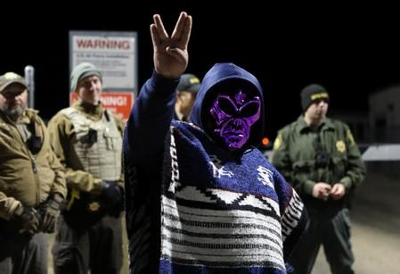 An attendee wears an alien mask at the gate of Area 51 as an influx of tourists responding to a call to 'storm' Area 51, a secretive U.S. military base believed by UFO enthusiasts to hold government secrets about extra-terrestrials, is expected in Rachel
