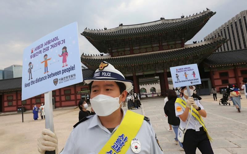 South Korean tourist police officers wearing face masks hold up social distancing signs at the Gyeongbok Palace in Seoul, South Korea, Wednesday, Sept. 30, 2020. - Ahn Young-joon