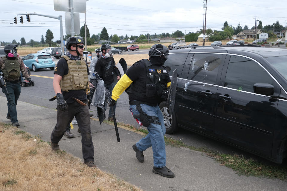 This Sunday, Aug. 22, 2021 photo, members of the far-right group Proud Boys surround a car they believe is driven by anti-fascist counter-protesters during clashes between the politically opposed groups in Portland, Ore. Police in Portland have been criticized that they did little to prevent violent clashes between right- and left-wing protesters on Sunday. (AP Photo/Alex Milan Tracy)