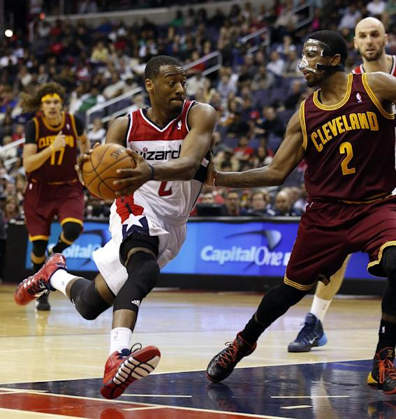 Washington Wizards guard John Wall (2) drives with the ball as he guarded by Cleveland Cavaliers guard Kyrie Irving (2) in overtime of an NBA basketball game on Saturday, Nov. 16, 2013, in Washington. The Cavaliers won 103-96 in overtime. (AP Photo/Alex Brandon)