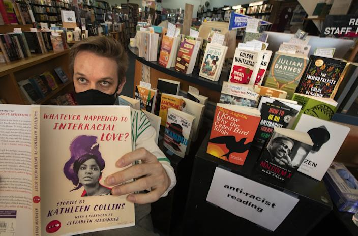 "Adam Lipman of Small World Books, on the Venice boardwalk, displays an offering from a new shelf devoted to antiracist reading. <span class=""copyright"">(Mel Melcon/Los Angeles Times)</span>"