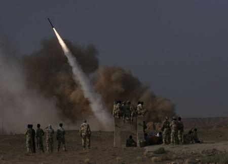 Members of Iran's revolutionary guard look at a surface to surface missile which is launched during a war game near the city of Qom, about 120 km (75 miles) south of Tehran June 28, 2011. REUTERS/Mehr News Agency/Rauf Mohseni