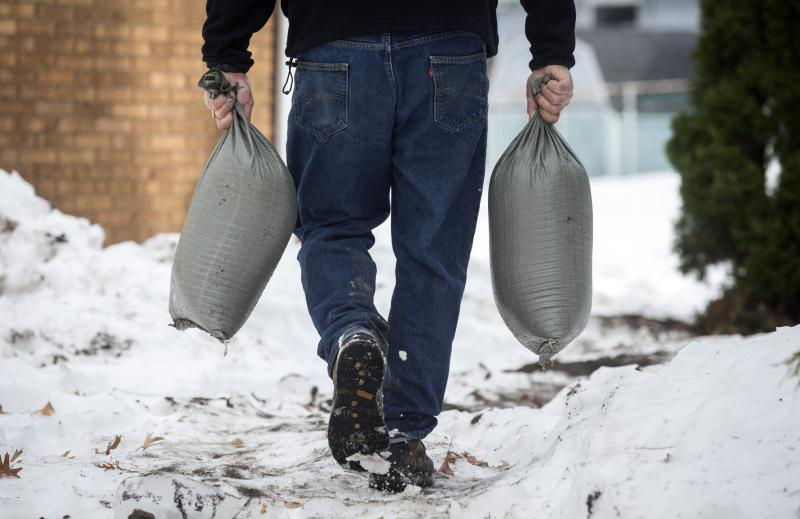Larry Miceli carries sandbags as he prepares his house for possible flooding following a massive snow storm in West Seneca