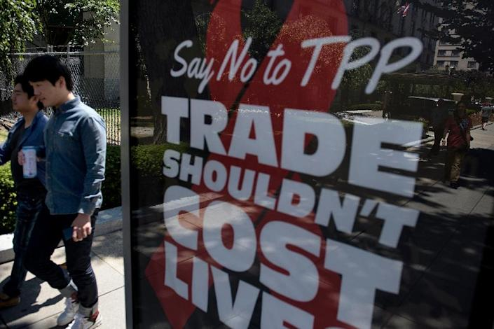 People walk by an advertisement protesting the passage of the Trans-Pacific Partnership in Washington, DC on July 23, 2015 (AFP Photo/Brendan Smialowski)