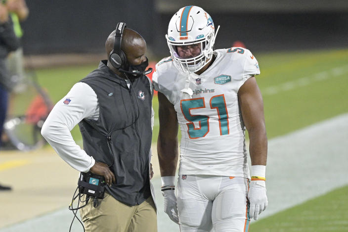 """FILE - In this Thursday, Sept. 24, 2020, file photo, Miami Dolphins head coach Brian Flores, left, talks with outside linebacker Kamu Grugier-Hill (51) on the sidelines during the first half of an NFL football game against the Jacksonville Jaguars, in Jacksonville, Fla. The Dolphins and Seattle Seahawks play on Sunday, Oct. 4. Everything has changed for Flores since the 2015 Super Bowl when he substituted Malcolm Butler, who made a game-saving interception of Russell Wilson to help New England edge Seattle. """"That stuff is in the past,"""" Flores said. """"Can't help us now."""" Then Patriots' linebackers coach, Flores is now in his second year as the Miami Dolphins' head coach. (AP Photo/Phelan M. Ebenhack, File)"""