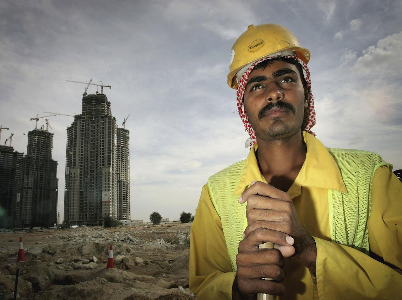 DUBAI, UNITED ARAB EMIRATES - DECEMBER 05:  A expatriate construction worker from Pakistan leans on his shovel on a building site in Dubai on December 5, 2006 in Dubai, United Arab Emirates. Construction in Dubai is on a massive scale and an estimated 20 percent of the world's cranes fill the skyline as the city establishes itself as one of the great tourist destinations of the world. Pakistani and Indian expatriate workers are employed by the construction companies and they send money back to their families at home.  (Photo by Chris Jackson/Getty Images)