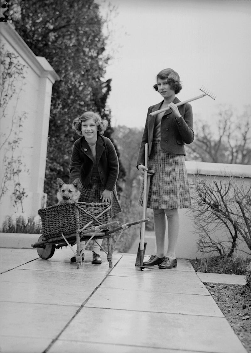 Princess Margaret and Queen Elizabeth II with gardening equipment and a pet corgi on a terrace of the Royal Lodge, Windsor, 1940.