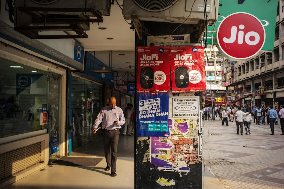 A pedestrian using a smartphone walks past advertising and signage for Reliance Jio Infocomm Ltd. at the Nehru Place IT Market in New Delhi, India on Tuesday, May 30, 2017. Reliance Communications Ltd.'s credit rating was cut deeper into junk territory by Moody's Investors Service, which cited its weak operating performance, high leverage and fragile liquidity position. Reliance Communications' troubles come amid intensifying competition among mobile phone carriers in India, fueled by the entry of Reliance Jio, launched by India's richest man Mukesh Ambani. Photographer: Sanjit Das/Bloomberg via Getty Images
