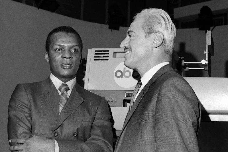 FILE - In this Jan. 3, 1970, file photo, baseball player Curt Flood, left, and Marvin Miller, Executive Director of the Baseball Players Association, wait inside ABC Television Studio before an appearance in New York. Flood set off the free-agent revolution 50 years ago Tuesday, Dec. 24, 2019, with a 128-word  letter to baseball Commissioner Bowie Kuhn, two paragraphs that pretty much ended the career of a World Series champion regarded as among the sport's stars but united a union behind his cause. (AP Photo/File)