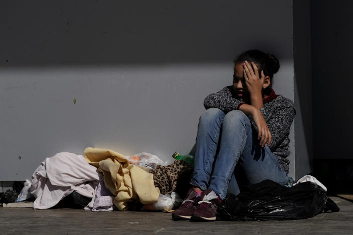 """A migrant shields herself from the sun while resting at a plaza near the McAllen-Hidalgo International Bridge point of entry into the U.S., after being caught trying to cross into the U.S. Thursday, March 18, 2021, in Reynosa, Mexico. The fate of thousands of migrant families who have recently arrived at the Mexico border is being decided by a mysterious new system under President Joe Biden. U.S. authorities are releasing migrants with """"acute vulnerabilities"""" and allowing them to pursue asylum. But it's not clear why some are considered vulnerable and not others. (AP Photo/Julio Cortez)"""